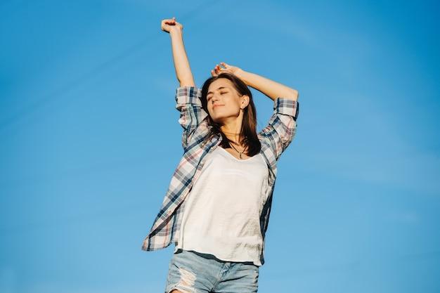 Opgetogen vrouw die zich uitstrekt genietend van de zon tegen de hemel