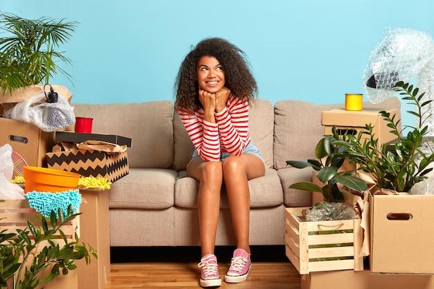 Opgetogen vrouwelijke appartementseigenaar heeft een dromerige uitdrukking