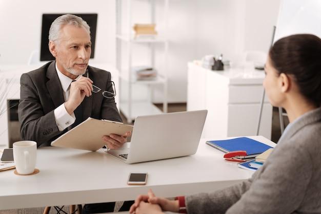 Opgetogen werknemer die aandachtig luistert naar zijn werknemer die de map in de linkerhand houdt terwijl hij op zijn werkplek zit