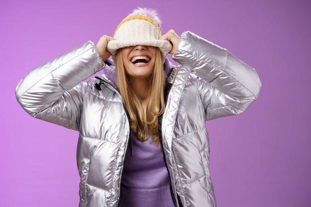 Opgetogen zorgeloze charmante gelukkige jonge blonde vrouw die pret verbergt gezicht