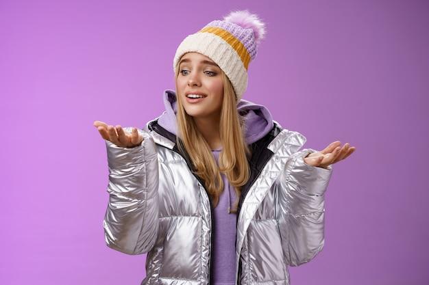 Opgetogen zorgzame mooie jonge blonde vrouw op zoek sneeuwvlok drop palm blik hand teder glimlachend koesteren mooi moment genieten van besneeuwde winterdag permanent blij paarse achtergrond.