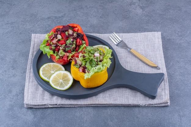 Opgevouwen tafelkleed onder schijfjes citroen met twee porties salades in plakjes paprika op een serveerschaal op marmeren ondergrond