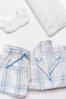 Opgevouwen warmwitte pyjama met blauw ruitjes- of strepenmasker voor slaapkussen