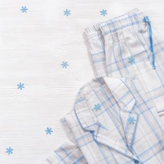 Opgevouwen warmwitte pyjama met blauwe ruitjes of strepen
