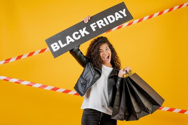 Opgewekt afrikaans meisje met zwart vrijdagteken en document het winkelen zakken die over geel met signaalband worden geïsoleerd