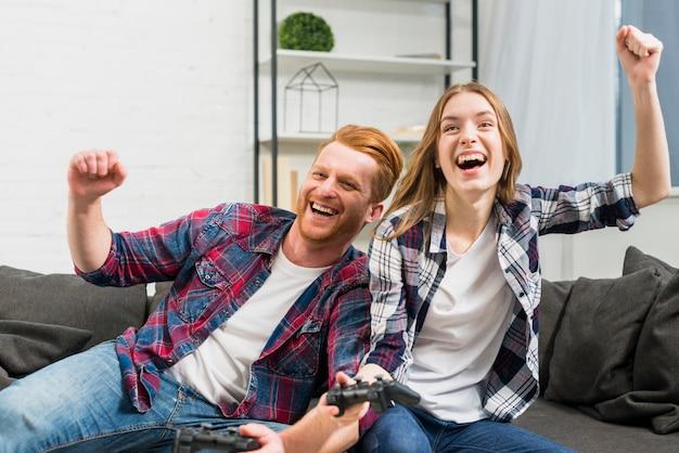 Opgewekt jong paar dat terwijl thuis het videospelletje toejuichen toejuicht