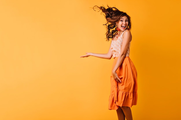 Opgewekt meisje dat met gember golvend haar op geel springt. studio portret van zalige jonge vrouw in oranje kledij dansen met een glimlach. Gratis Foto