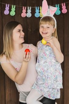 Opgewekt meisje met moeder die paaseieren houdt