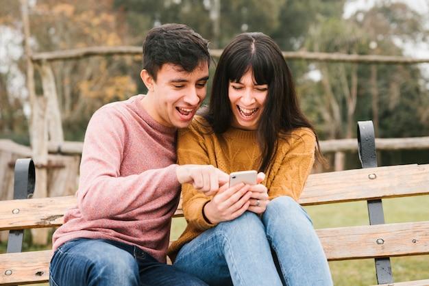 Opgewekt paar lachen die smartphone bekijken