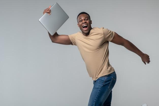 Opgewekt persoon. vrolijke jonge donkere man met laptop zwaaiende handen vreugde in studiofoto