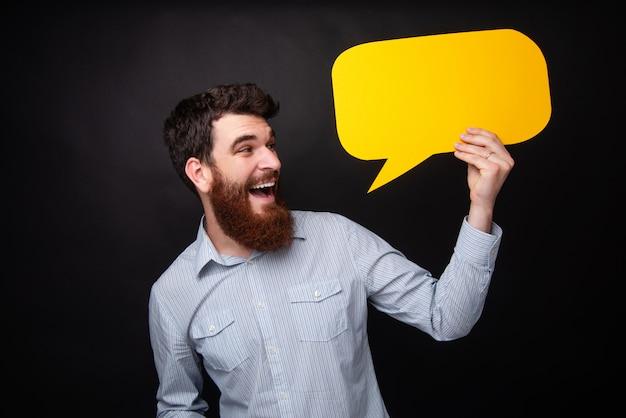 Opgewekt portret van knappe gebaarde kerel met baard, houdend een gele lege bellentoespraak, die zich over donkere geïsoleerde achtergrond bevinden