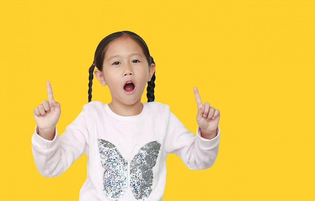 Opgewekt weinig aziatisch kindmeisje dat omhoog geïsoleerde wijsvinger twee richt