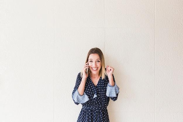 Opgewekte aantrekkelijke jonge vrouw die op cellphone spreekt