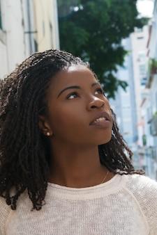Opgewekte afrikaanse amerikaanse vrouwelijke toerist die in oude stad loopt