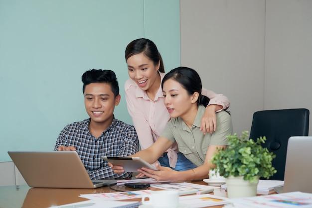 Opgewekte aziatische collega's die laptop het scherm samen in bureau bekijken