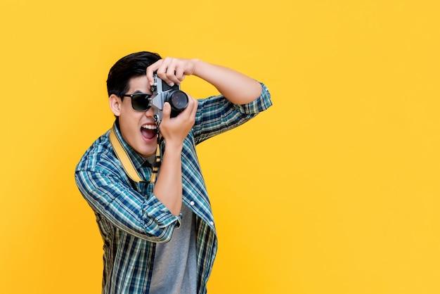 Opgewekte aziatische toeristenfotograaf die foto met camera nemen