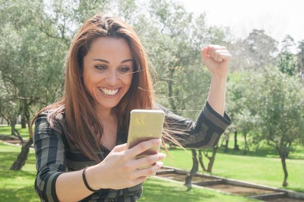 Opgewekte euforische dame met smartphone die groot nieuws viert