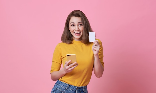 Opgewekte gelukkige jonge vrouw die mobiele telefoon en creditcard houdt die over roze wordt geïsoleerd