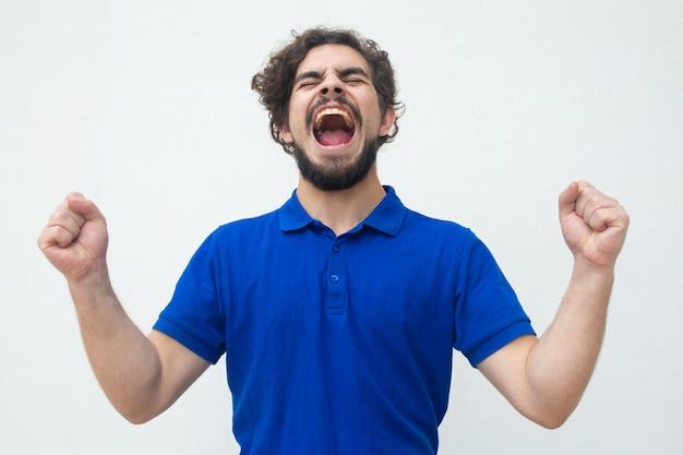 Opgewekte gelukkige kerel die voor vreugde schreeuwt