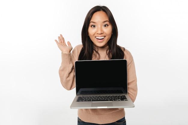 Opgewekte geschokte vrouw die vertoning van laptop toont