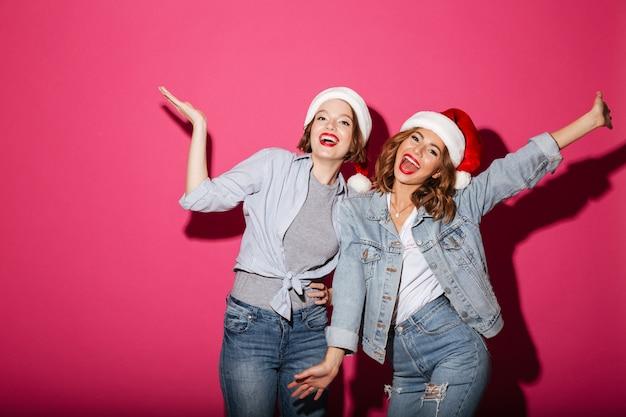 Opgewekte glimlachende twee vrouwenvrienden die de hoeden van kerstmissanta dragen