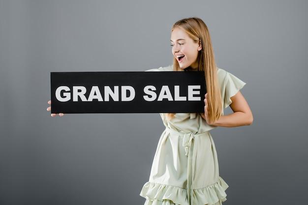 Opgewekte glimlachende vrouw met groot die verkoopteken over grijs wordt geïsoleerd