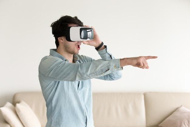 Opgewekte jonge kerel die virtuele werkelijkheid ervaart die vr headse draagt