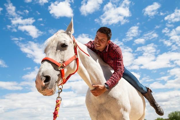 Opgewekte jonge kerel in toevallige uitrusting die en hals van wit paard glimlachen omhelzen tijdens rit op gebied op bewolkte dag
