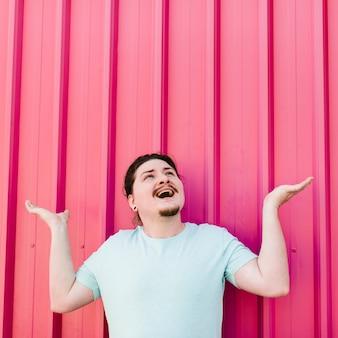 Opgewekte jonge mens die omhoog schouderophalend tegen roze golfijzerblad kijken