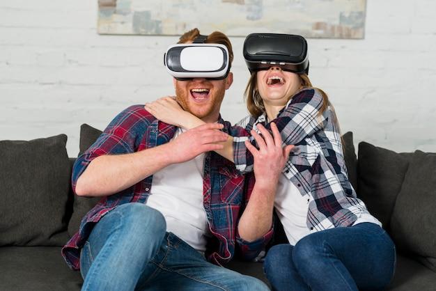 Opgewekte jonge paarzitting op bank die een vrhoofdtelefoon met behulp van en virtuele werkelijkheid ervaart