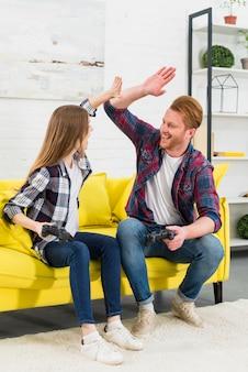 Opgewekte jonge paarzitting op holdingsjoystick van de bankholding in hand die high-five geven aan elkaar