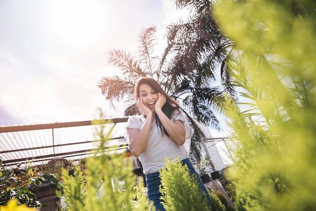 Opgewekte jonge vrouw die installatie in serre bekijkt