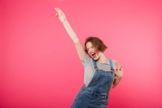 Opgewekte jonge vrouw die over roze wordt geïsoleerd