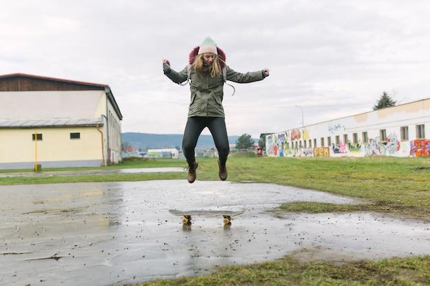 Opgewekte jonge vrouw die over skateboard springt