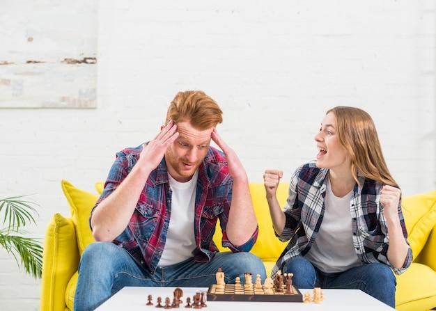 Opgewekte jonge vrouwenzitting met haar vriend die na het winnen van het schaakspel toejuichen
