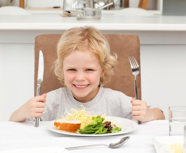 Opgewekte jongen die vorken houden om deegwaren en salade te eten