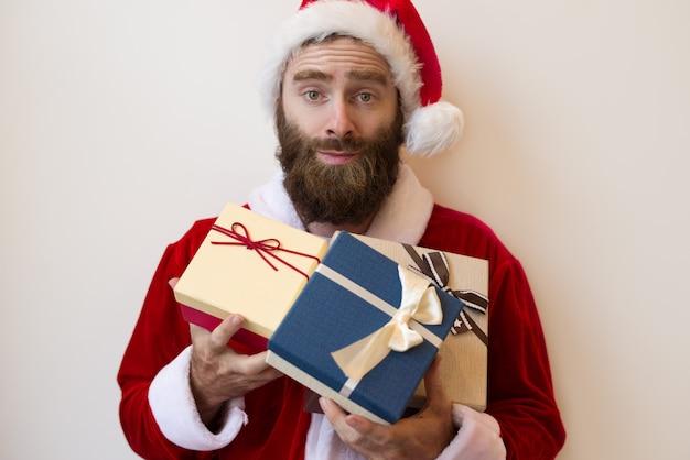 Opgewekte kerel die het kostuum van de kerstman draagt en de dozen van de gift houdt