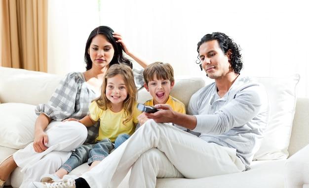 Opgewekte kleine jongen die op tv met zijn familie let