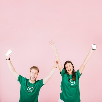 Opgewekte man en vrouw die met smartphone hun wapens opheffen