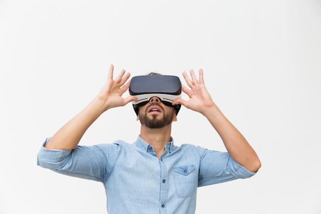 Opgewekte mannelijke gebruiker die vr-bril draagt, apparaat aanraakt