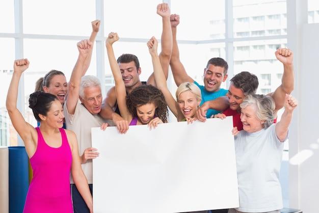 Opgewekte mensen die leeg aanplakbord houden bij gymnastiek