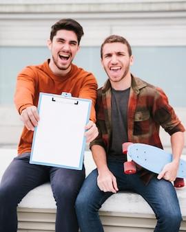 Opgewekte moderne mannelijke vrienden met klembord en kruiser