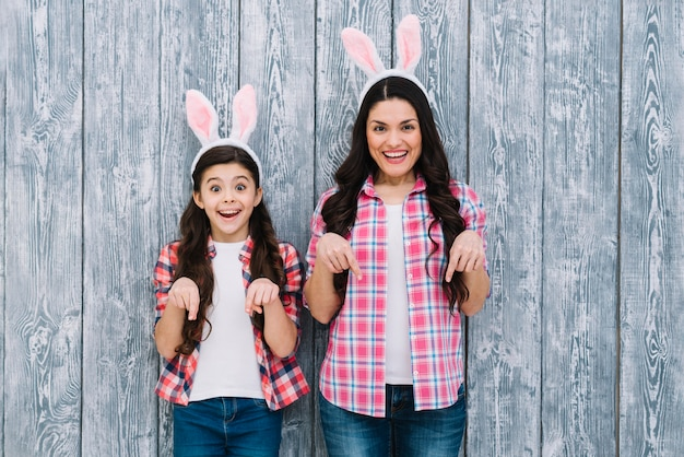 Opgewekte moeder en dochter die met konijntjesoren de vinger naar beneden tegen houten achtergrond richten