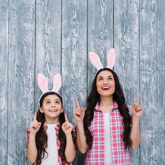 Opgewekte moeder en dochter die met konijntjesoren de vinger naar omhoog tegen houten achtergrond richten