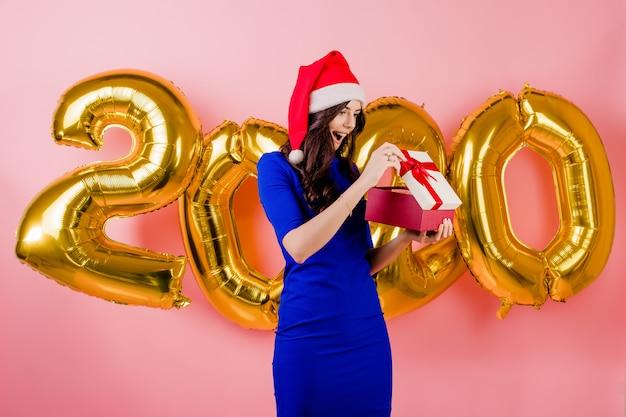 Opgewekte mooie vrouw die santahoed het openen giftdoos voor nieuwe jaar 2020 ballons draagt die over roze worden geïsoleerd