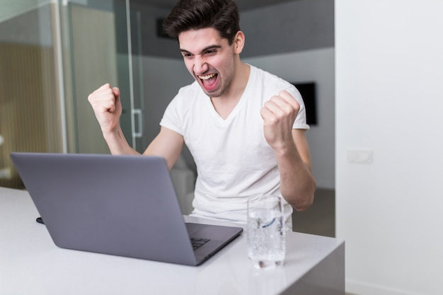 Opgewekte ondernemer die met laptop werken en goed nieuws online op werkplaats thuis lezen