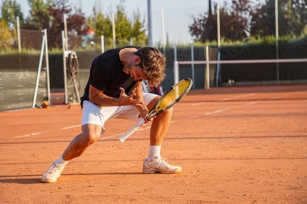 Opgewekte sportieve mens die met racket triomf op tennisbaan vieren in helder zonlicht expressief kijken.