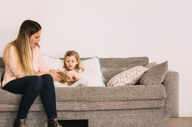 Opgewekte vrouw die dochter met lezing helpt