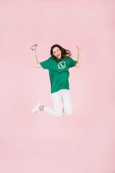 Opgewekte vrouw die met cellphone over roze achtergrond springt