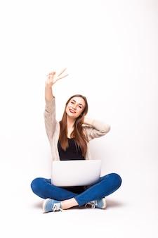 Opgewekte vrouw die met laptop van succes op wit geniet